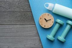 Hora para ejercitar el reloj y la pesa de gimnasia con el fondo de la estera de la yoga Fotos de archivo libres de regalías