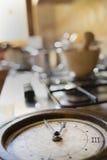 Hora para el almuerzo con un reloj viejo en un estufa-top Fotografía de archivo