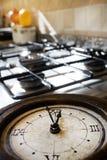 Hora para el almuerzo con un reloj viejo en un estufa-top Fotografía de archivo libre de regalías