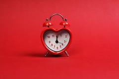 Hora para el amor Despertador en forma de corazón rojo en fondo rojo Fotos de archivo