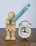 Hora para el concepto de la medicación con el hombre de madera y una jeringuilla Foto de archivo libre de regalías