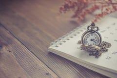 Hora para esperar con el reloj de bolsillo del vintage en el calendario y el W Imagen de archivo