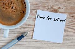 HORA PARA la escritura de la ACCIÓN en la taza cercana de papel de café de la mañana en el lugar de trabajo o la tabla de madera Imagen de archivo