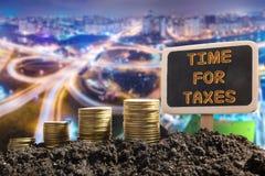 Hora para los impuestos - concepto financiero de la oportunidad Monedas de oro en pizarra del suelo en fondo urbano borroso Fotos de archivo libres de regalías