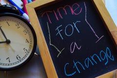 Hora para a mudança a em escrito à mão colorido da frase no quadro, no despertador com motivação e nos conceitos da educação fotografia de stock