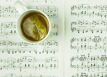 Hora para a pausa e resto com o copo do chá e do conceito das notas da música imagem de stock