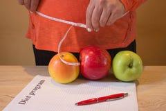 Hora para a perda de peso do emagrecimento da dieta Mulher com medida da fita e a maçã Faça dieta o conceito Fotografia de Stock Royalty Free