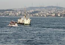 Hora punta en el Bosphorus Dos buques de pasajeros cruzan a los viajeros que llevan del estrecho de ambos lados foto de archivo