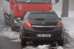 Hora Svateho Sebestiana, república checa - 25 de novembro de 2018: carro e camion no centro da vila em montanhas nevoentas do min imagem de stock