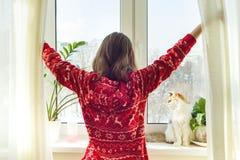 Horaire d'hiver à la maison, jeune fille dans des pyjamas chauds d'hiver avec un chat regardant la fenêtre photographie stock