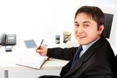 Horaire de sourire de planification d'homme d'affaires en agenda Images stock