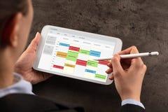 Horario de la mujer de negocios su programa sobre la tableta fotografía de archivo libre de regalías