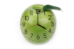 Horas contra manzana verde Imagenes de archivo