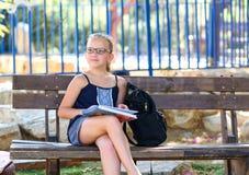 Horas de ver?o que relaxam - livro de leitura da menina exterior no dia morno fotografia de stock