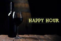 Horas felices Un vino rojo del opf de la botella y un vidrio con el barril en vagos Fotos de archivo libres de regalías