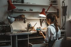 Horas longas do trabalho Opinião traseira o joalheiro fêmea novo que faz o produto novo em sua oficina da joia imagens de stock