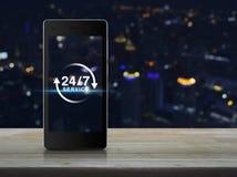 24 horas mantienen el icono en la pantalla elegante moderna del teléfono en etiqueta de madera Foto de archivo libre de regalías
