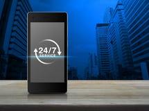 24 horas mantienen el icono en la pantalla elegante moderna del teléfono en etiqueta de madera Imagenes de archivo