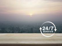 24 horas mantienen el icono en la tabla de madera sobre la vista aérea del citysc Imágenes de archivo libres de regalías