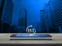 24 horas prestam serviços de manutenção ao ícone na tela esperta moderna do telefone na tabela Imagens de Stock