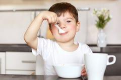 Horiontal-Porträt des attraktiven männlichen Kindes isst köstlichen Brei mit der Milch, zurechtgemacht im zufälligen weißen T-Shi stockfotos