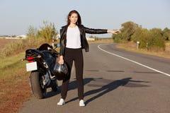 Horiontal strzał fachowy żeński rowerzysta stoi blisko brocken motocykl, jest ubranym skórzaną kurtkę, trzyma hełm, hitchhikes na zdjęcia royalty free