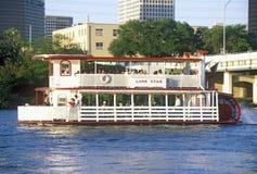 Horisont av Austin, TX, den statliga capitolen med Coloradofloden och riverboaten i förgrund Arkivfoton