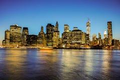 Horisont av Manhattan på solnedgången som stängs till natten Trevlig sikt efter Brooklyn royaltyfri fotografi