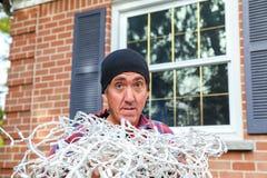 Horisontal av en man med tilltrasslade julljus fotografering för bildbyråer