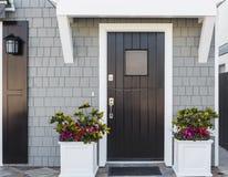 Horisontal av svart ytterdörr till familjhemmet Arkivfoton