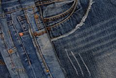 Horisontal denim background, assortment of blue jeans, pile of b. Lue jeans, denim textures Royalty Free Stock Photo