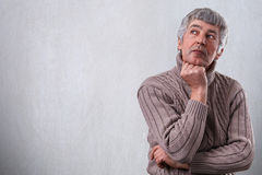 A horisontal portrait of senior man having serious face dreaming about something looking aside holding his hand under his chin. Th Stock Photos