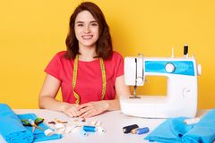 Horisontal portrait of young pretty woman in casual red t shirt with sewing machine and measuring tape on neck, looks directly at royalty free stock photography