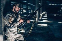 Horisontalbild av soldaten som mycket nästan står kolonnen med hans baksida och laddar upp riflle Han är i en stor hangar Royaltyfria Foton