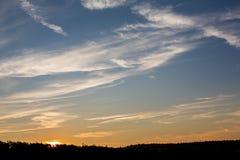 Horisontalcloudscape av i lager moln på solnedgången med solen Royaltyfri Foto