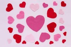 Horisontaldag för kortvalentin` s Röda och rosa hjärtor på ett ljus - rosa bakgrund Arkivfoto