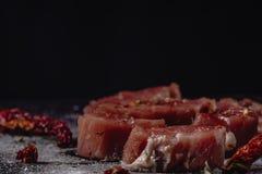Horisontalfoto av rått kött för grisköttfläskkarré Rått kött är på lantligt mörkt taktpinnebräde, med peppar och saltar arkivbild
