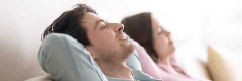 Horisontalfotogift par med stängda ögon som vilar på soffan royaltyfri bild