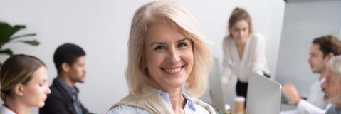 Horisontalfotostående av den höga affärskvinnan som ler se kameran royaltyfri foto