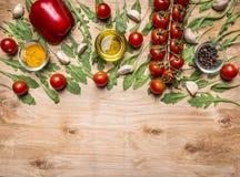 Horisontalgräns med grönsaker, olja, körsbärsröda tomater på en filial, peppar, smaktillsats, arugula, vitlökgräns, med textområd Royaltyfri Bild