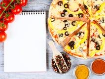 Horisontalmatbaner med körsbärsröda tomater, klippt pizza, kryddan och anteckningsboken på träbakgrund Tomt avstånd för text Royaltyfri Bild