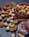 Horisontalnärbild av muttrar, kasjuer och kanderade frukter, som sprids på tabellen Närliggande är en träask med en grupp av royaltyfri bild