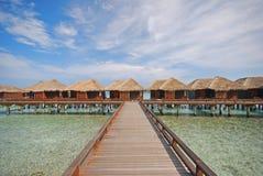 Horisontalpittoresk sikt av träbrogångbanan som leder till en rad av den lyxiga Overwater villan royaltyfria foton
