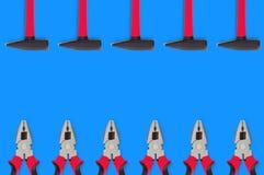 Horisontalrader av metallhammare och plattång med svarta och röda gummihandtag på den blåa tabellen i arbetsrum Top beskådar Repa royaltyfria bilder