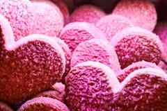 Horisontalrosa bakgrund för valentinsockerkaka - hjärta formade kakor som överlappar - royaltyfria foton