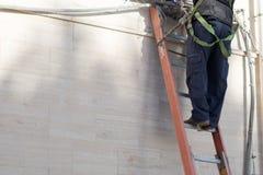 Horisontalsikt av en Tecnician som arbetar på en stege med säkerhet T arkivfoto