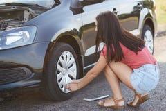 Horisontalsikten av den erfarna kvinnliga chauffören försöker att fixa det plana gummihjulet, använder special utrustning, löser  Royaltyfri Bild
