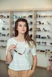 Horisontalskott av den gulliga kvinnan med stilfullt frisyranseende i optiskt lager, medan välja solglasögon Varje flicka bör Royaltyfri Bild