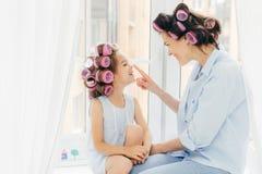Horisontalskott av den nätta unga modern och dottern med hårrullar fotografering för bildbyråer