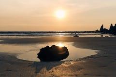 Horisontalskott av en stor kontrastkontur av en sten mot bakgrunden av en solig solnedgång, havet och den sandiga stranden royaltyfri foto